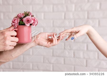Man presenting roses in crimson cup to woman 34393226