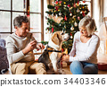 Senior couple with dog in front of Christmas tree 34403346