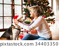 Senior woman with her dog at the Christmas tree. 34403350