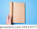 Top view of hands holding a blank book  34419377