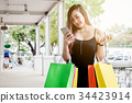Woman using phone enjoying shopping Street 34423914