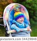 Baby boy in stroller in autumn park 34429846