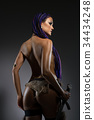 Horsewoman with African braids cropped rearview 34434248