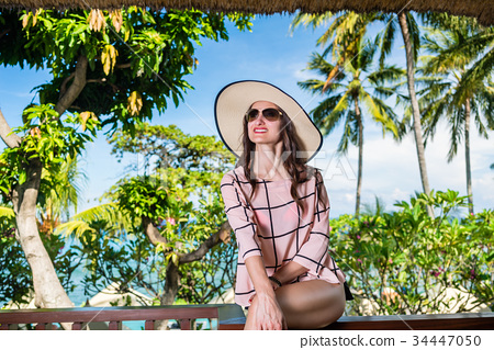 Woman sitting in front of palm trees in summer 34447050
