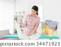 housewife using ironing board folding clothing 34471923