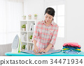 pretty woman worker ironing all wrinkled clothing 34471934