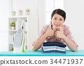 happy housekeeper woman ironing family clothing 34471937