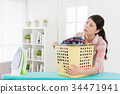 attractive housewife holding laundry basket 34471941