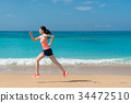 beautiful young athletic woman running on beach 34472510
