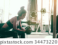 Asian woman sitting at gym club and listen music 34473220