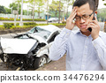 driver talking on mobile phone with crash car 34476294