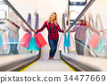 Young woman with shopping bags on escalator in the fashion store 34477669
