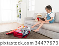 beautiful kid girl sitting on living room sofa 34477973