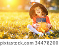 child girl with pumpkin outdoors in halloween 34478200