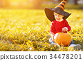 baby boy with pumpkin outdoors in halloween 34478201