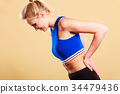 Fit woman suffering from back pain 34479436
