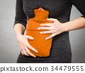 Girl having stomach ache, holding hot water bottle 34479555