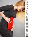 Girl having stomach ache, holding hot water bottle 34479557