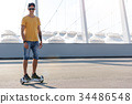 Cheerful young man riding on gyroscope 34486548