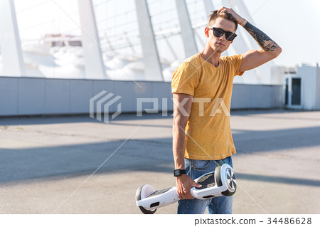 Orderly teenager keeping hoverboard in arm 34486628