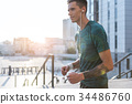 Outgoing male runner hearing song at street 34486760