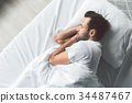 Cute young man sleeping on bed 34487467