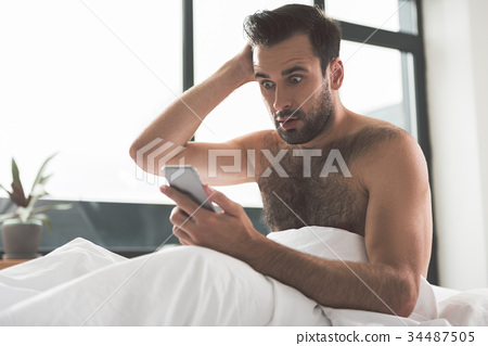 Shocked guy receiving bad news by mobile phone 34487505
