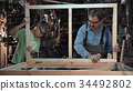 Carpenter with grandson making window 34492802