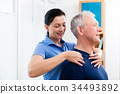 Physio giving shoulder massage to patient 34493892