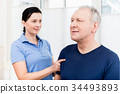 Physio giving shoulder massage to patient 34493893