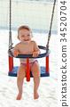 Joyful baby girl plays with the swing 34520704