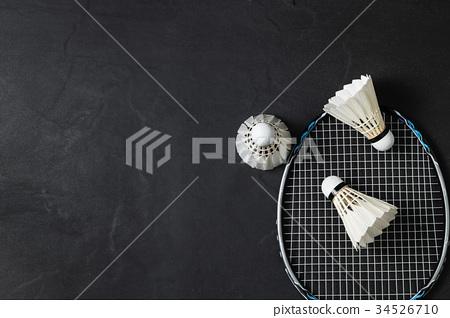 Shuttlecocks and badminton racket on black  34526710