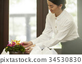The staff is checking the flowers on the table. 34530830