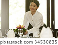 Smiling waitress is setting flowers on the dining table in Thai restaurant 34530835