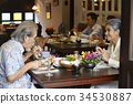 A senior couple is enjoying the food together at a restaurant. 34530887