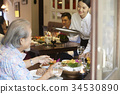 the waitress is serving water to a senior couple in a restaurant 34530890