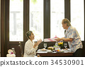 Asian senior man giving his surprised wife a gift at restaurant 34530901