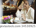 an older woman is smiling while enjoying a meal in a restaurant 34530925