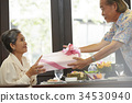 a senior man is smiling happily when giving a gift for his wife 34530940