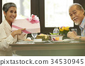 a senior woman is pointing a gift box while sitting in a restaurant with her husband 34530945
