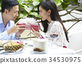 young man is giving a gift box to his girlfriend in a restaurant 34530975