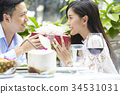 young woman is smiling when taking a present from her boyfriend in a restaurant 34531031