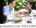 An Asian woman is feeling shy when her boyfriend is giving her a gift. 34531080