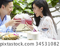 An Asian man is giving a gift to his girlfriend in a restaurant. 34531082