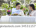 The couple is sitting and eating very happily together at a restaurant 34531157