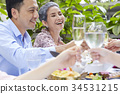 a handsome man and his mother are drinking with family in a restaurant 34531215