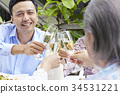 a handsome guy is raising wine glass to cheer up with his family in a restaurant 34531221