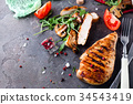Grilled chicken fillets on slate plate. 34543419