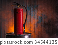 Fire extinguisher on old rusty barrel 34544135