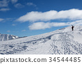 Skier with skis go up to top of mountain 34544485